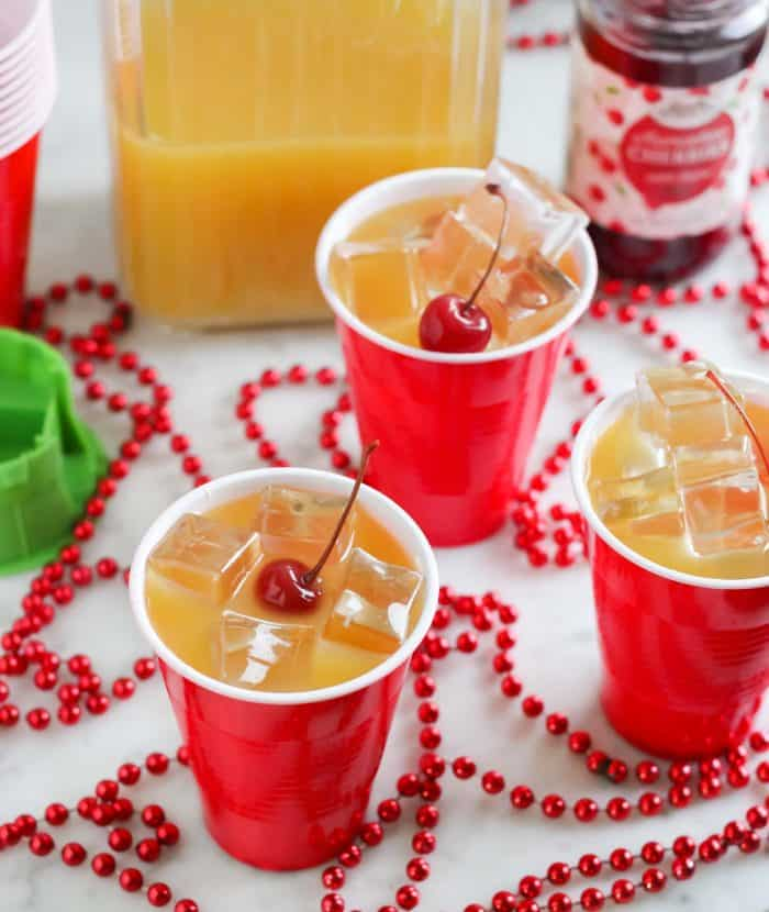 red beads on counter with yellow hammer drinks in red cups with cherries on top, pitcher of yellowhammers