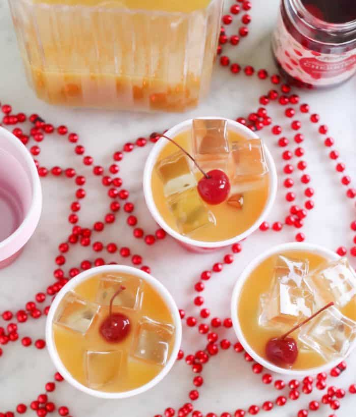 overhead view of 3 yellow hammer drinks with cherries, red beads, pitcher and cherries