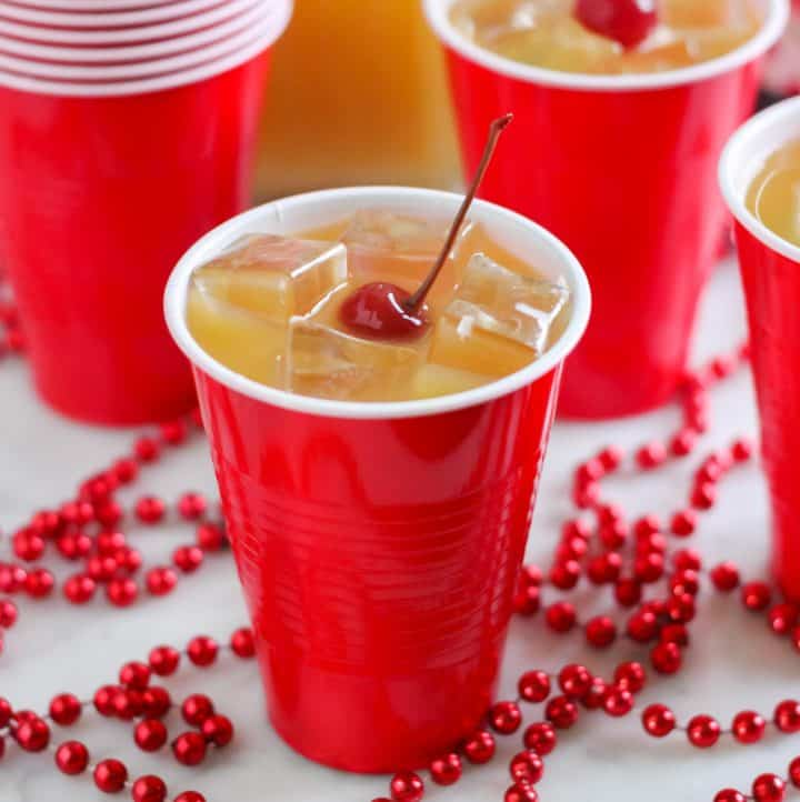 yellow hammer drink in red cup with cherry on top, red beads