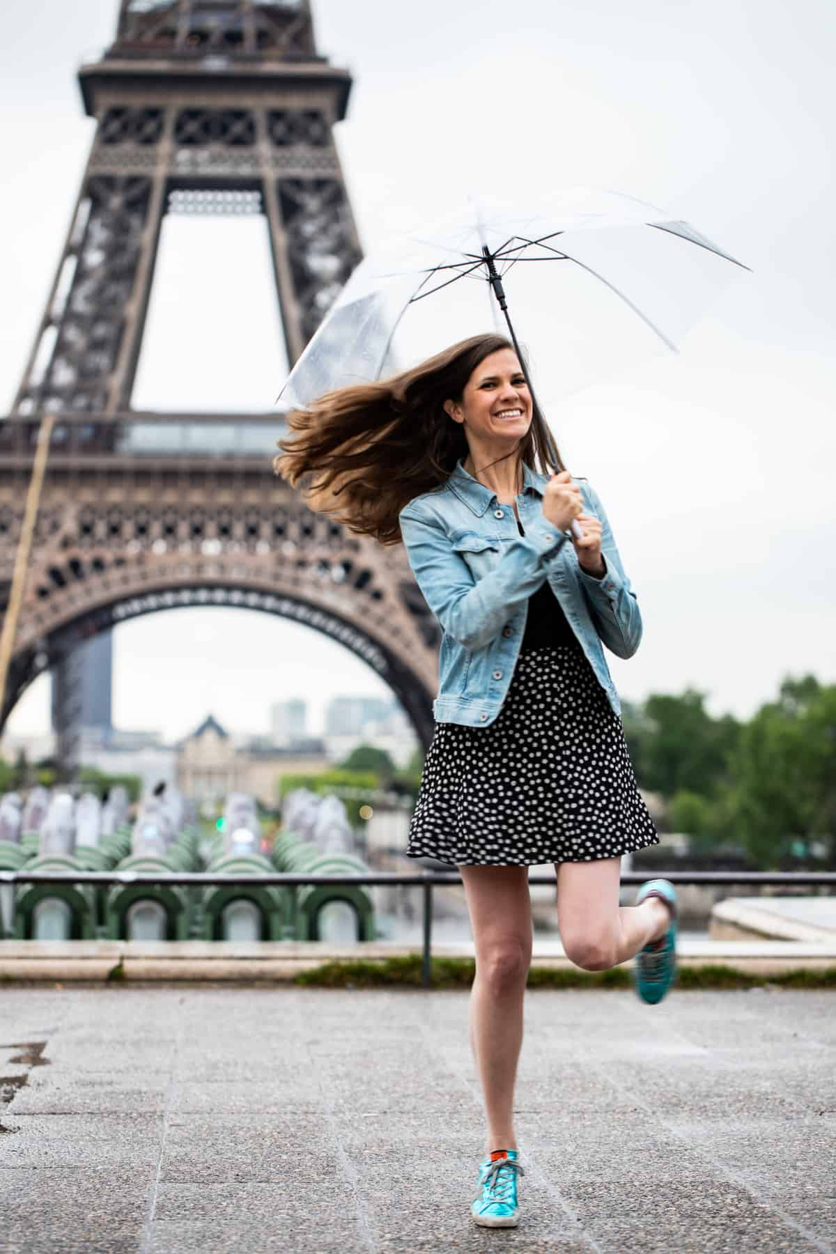 Meme (a brunette female) is holding umbrella and spinning around in front of the Eiffel Tower wearing a denim jacket, skirt, and blue shoes
