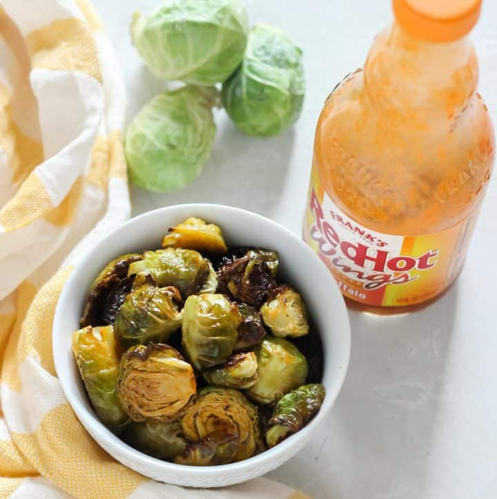 white bowl with roasted Brussels sprouts covered in buffalo sauce, fresh Brussels sprouts, bottle of buffalo sauce, yellow and white striped dish towel