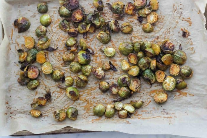 parchment lined baking sheet with roasted Brussels sprouts covered in buffalo-butter sauce