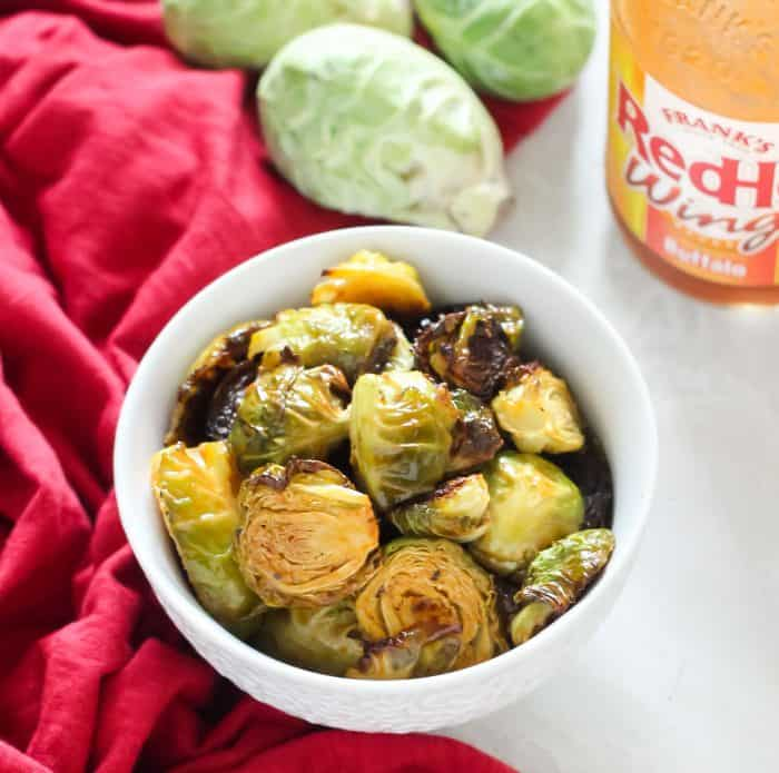 red towel with white bowl of roasted Brussels sprouts with buffalo sauce and fresh Brussels sprouts