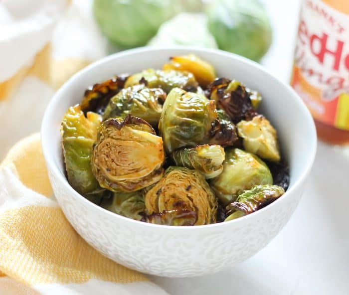 white bowl of buffalo Brussels sprouts with white and yellow striped dish towel