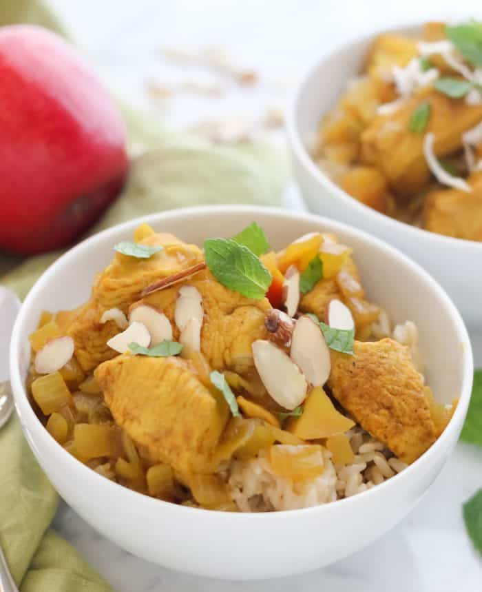 white bowl of healthy chicken curry topped with sliced almonds and fresh mint, another bowl in the background with an apple