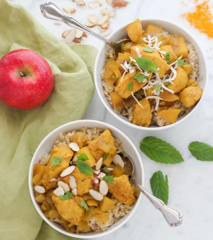 two white bowls of chicken curry topped with fresh mint and sliced almonds with silver spoons on green napkin with apple, curry powder, sliced almonds and fresh mint