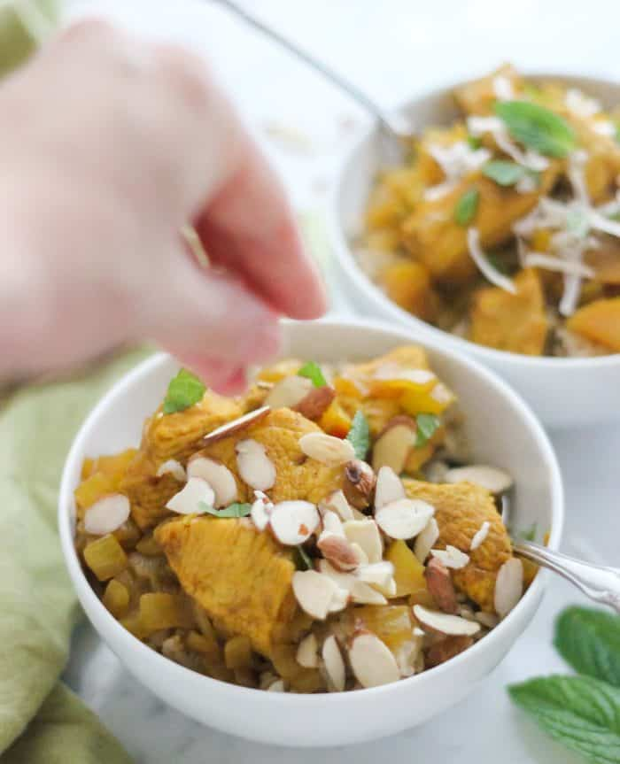 hand sprinkling chopped almonds over a bowl of chicken apple curry with a silver spoon, another bowl is in the background