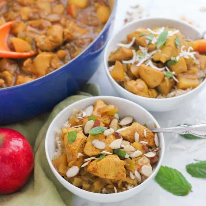 two white bowls of chicken apple curry topped with sliced almonds and fresh mint, apple, and blue pot with more chicken curry sauce