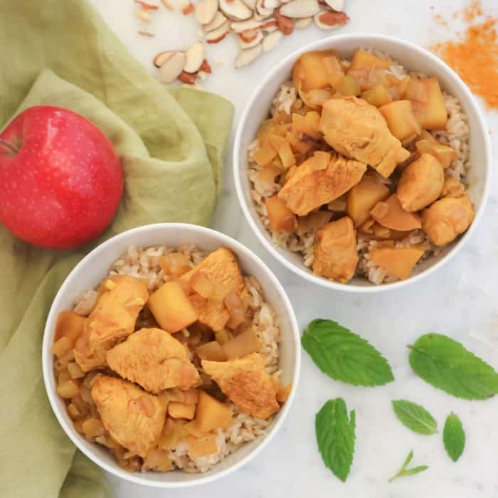 two white bowls with chicken curry served over rice on green napkin with sliced almonds, mint leaves and apple