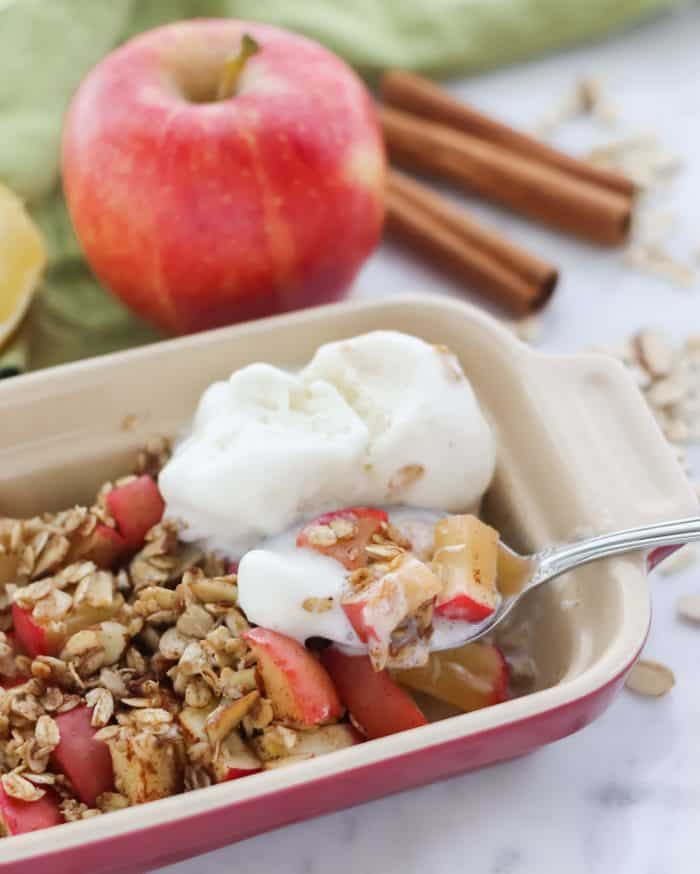 red and cream casserole dish with microwave baked apple topped with vanilla ice cream, spoon holding apples, apple, cinnamon sticks