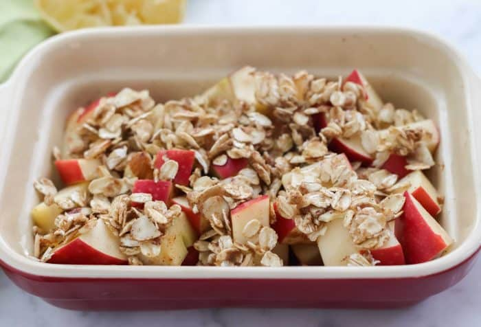 red and cream casserole dish with apples topped with oats, butter and brown sugar