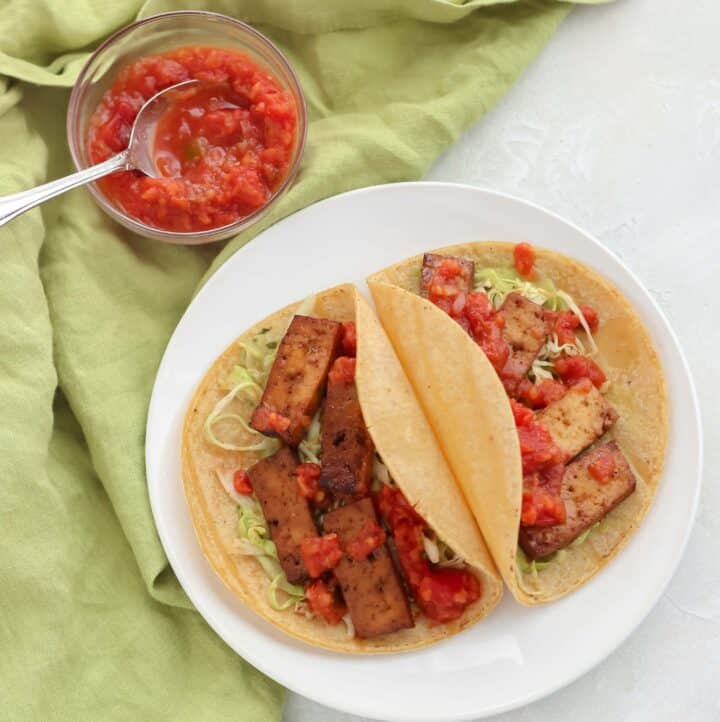 small bowl of salsa on green napkin with plate of two tacos with tofu and slaw