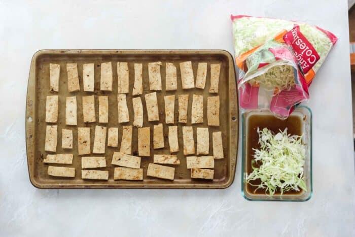 tofu on a baking sheet, bag of coleslaw, coleslaw in marinade