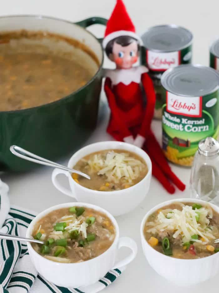 three white cups of cheeseburger chowder with spoons, canned veggies, elf on the shelf, pot of soup