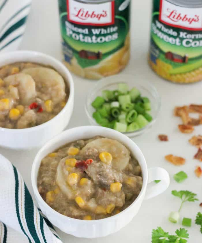 cheeseburger chowder in white cups with green and white napkin and bacon bits, green onions, canned veggies