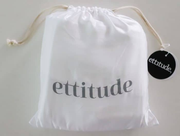 white drawstring bag with ettitude sheet set