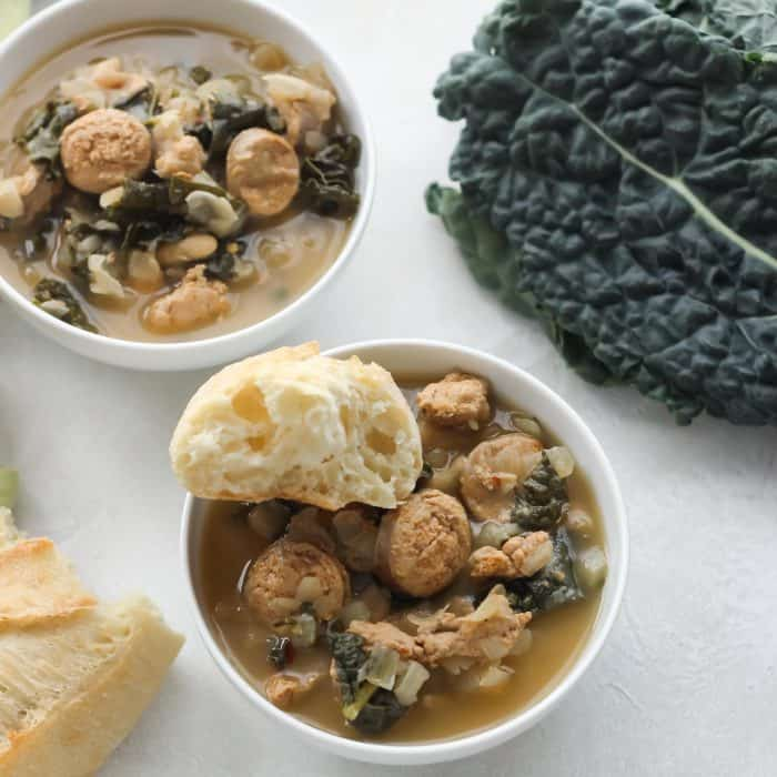 white bowls with sausage kale soup with french bread and fresh kale