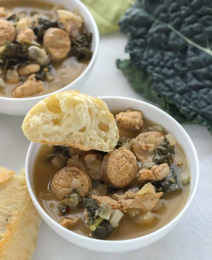 bowl of sausage white bean kale soup with piece of bread, another bowl of soup and fresh kale