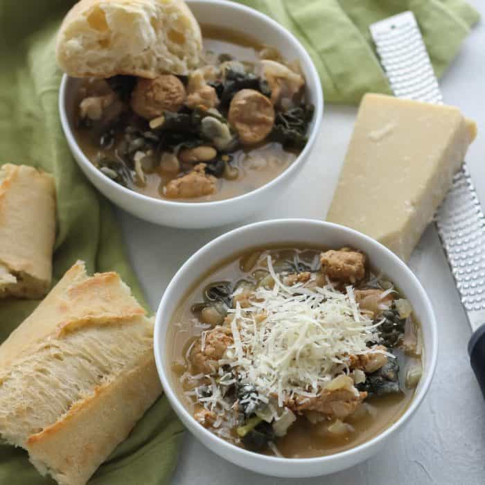 two bowls of sausage kale white bean soup topped with parmesan cheese, with french bread and fresh kale
