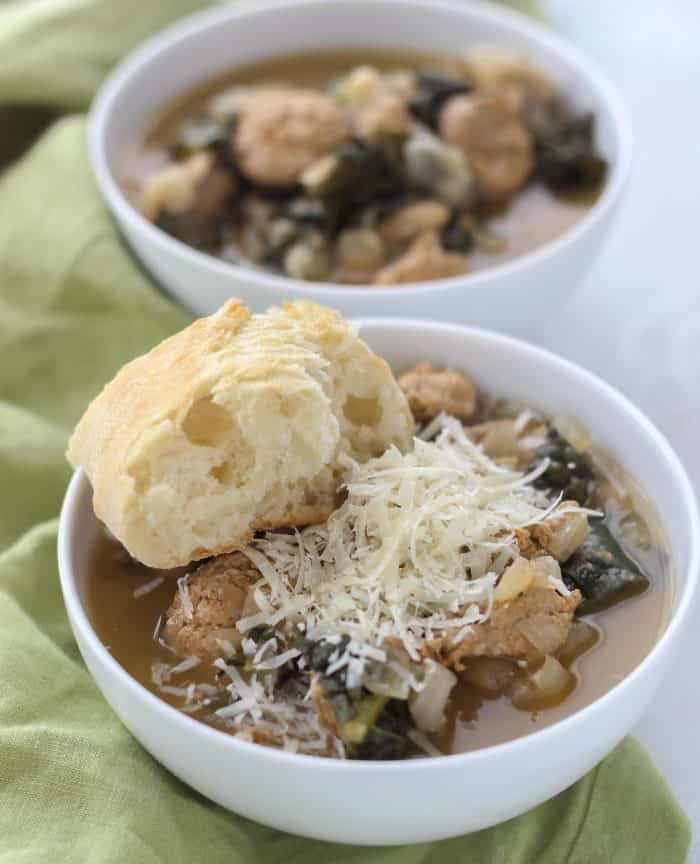 two white bowls of white bean sausage kale soup topped with parmesan cheese and slice of bread