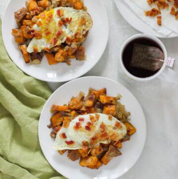white countertop with green napkin and two plates of sweet potato bacon hash topped with fried eggs and a mug of tea with plate of bacon crumbles