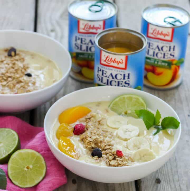 smoothie in white bowls topped with peaches, granola, lime, mint, canned peaches