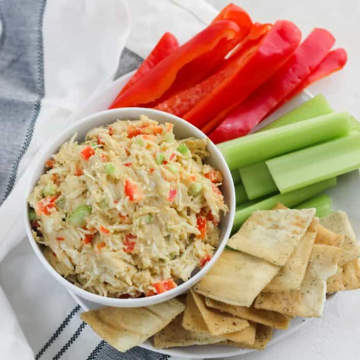 white bowl with hummus chicken salad surrounded by red bell peppers, celery, and pita chips on a white napkin