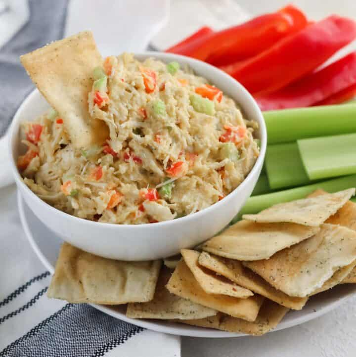 white and black napkin with plate of pita chips, celery, and red bell peppers, and a bowl of chicken salad with pita chip in bowl