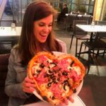 brunette female holding a heart shaped pizza in a Parisian cafe