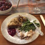 fancy china with turkey, cranberry sauce, dressing, sweet potato casserole, green beans and silver fork with rosé and grapes on table